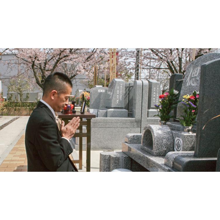 お墓で手を合わせる人